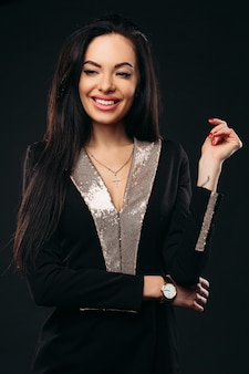 Risa belleza en vestido negro y dorado.