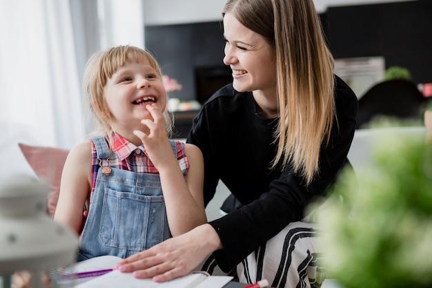 Risa de madre e hija haciendo los deberes