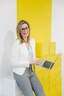 Risa de mujer con computadora portátil en la oficina