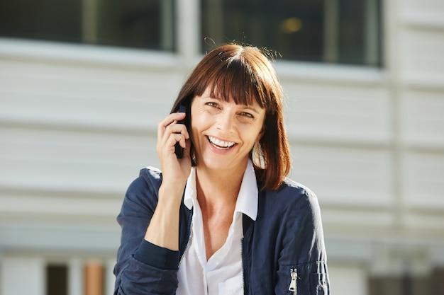 Risa mujer hablando por teléfono inteligente fuera