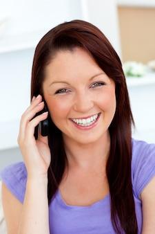 Risa mujer joven hablando por teléfono en casa