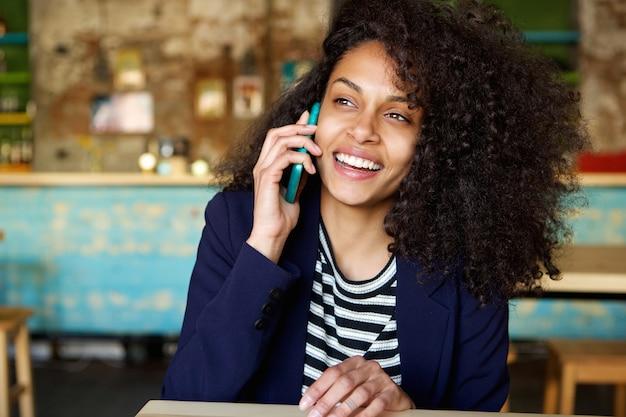 Risa mujer joven hablando por teléfono celular en el café