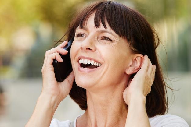 Risa mujer mayor hablando por teléfono inteligente fuera