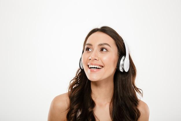 Risa mujer morena en auriculares escuchando música y mirando a otro lado sobre gris