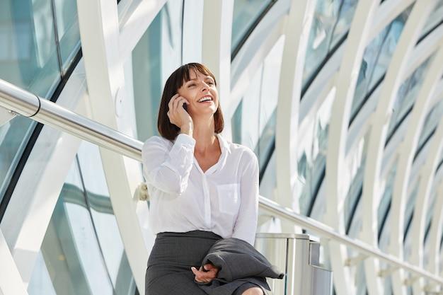 Risa mujer de negocios hablando por teléfono inteligente en la terminal