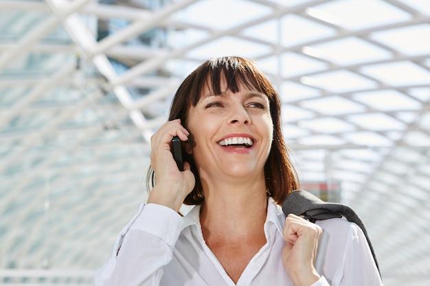 Risa mujer de negocios hablando por teléfono móvil en la estación