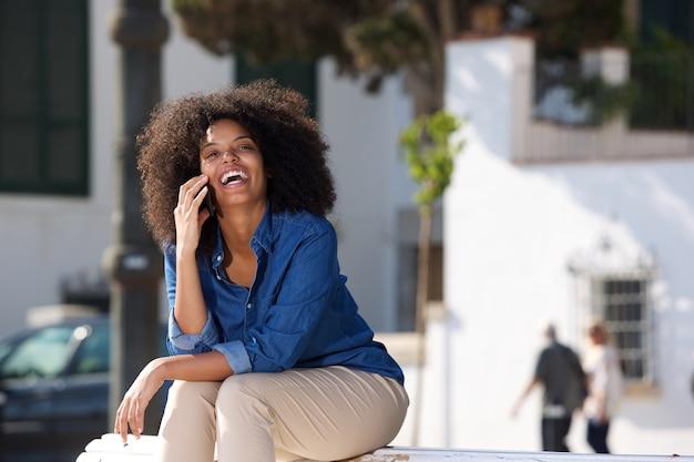 Risa mujer sentada afuera hablando por teléfono móvil