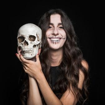 Risa mujer sosteniendo el cráneo