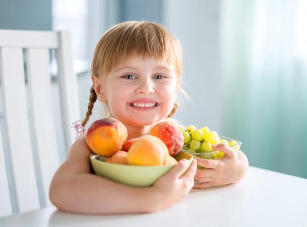 Risa de niña con melocotones, uvas y sandía en la mesa
