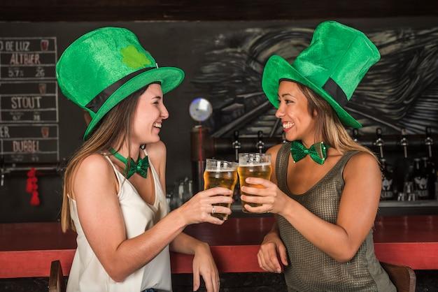 Risas de mujeres jóvenes en los sombreros de san patricio haciendo sonar vasos de bebida en la barra del bar
