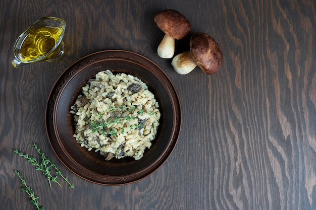 Risotto con arroz arborio, caldo, champiñones y tomillo sobre mesa de madera marrón oscuro