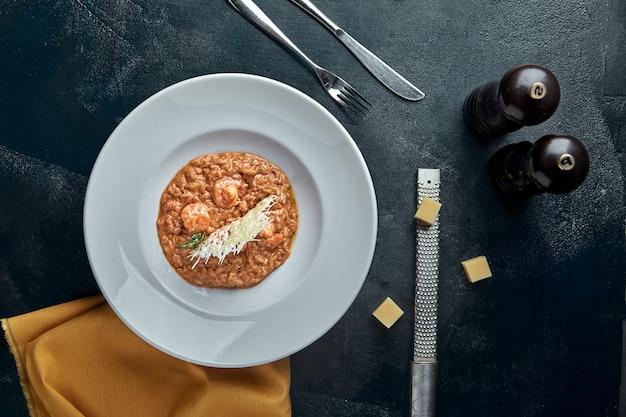 Risotto con carne de cerdo y queso en plato blanco