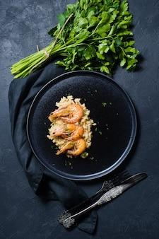 Risotto italiano con camarones en un plato negro, un manojo de cilantro.