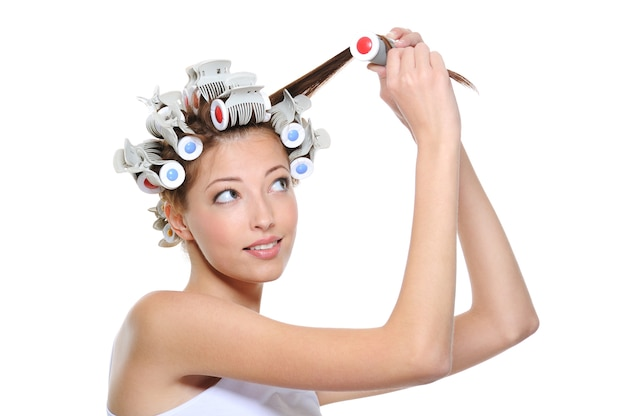 Rizado de cabello por la joven bella mujer en blanco