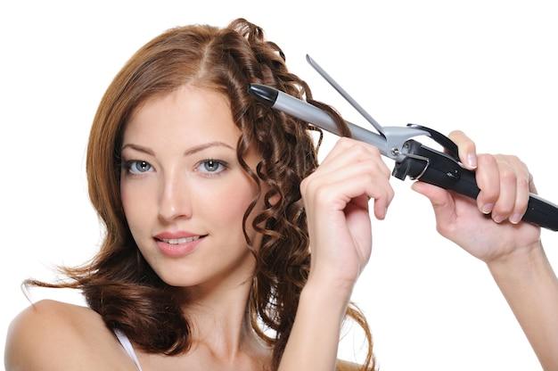 Rizar el cabello morena mujer con rodillo aislado en blanco