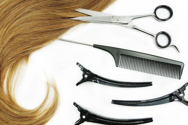 Rizo de herramientas de peluquería y cabello aislado en blanco