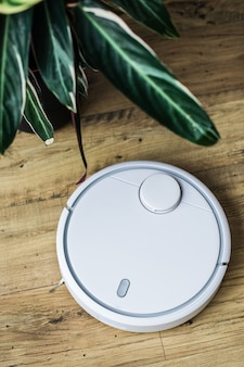 Robot aspirador sobre suelo de madera. la vista desde la cima. concepto de casa inteligente limpieza automatica