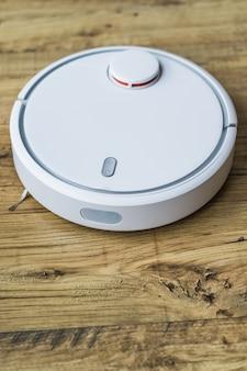Robot aspirador sobre suelo de madera. vista lateral. concepto de casa inteligente limpieza automática.