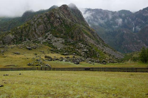 Roca envuelta en niebla, cubierta de pasto verde, valla de madera debajo de la montaña