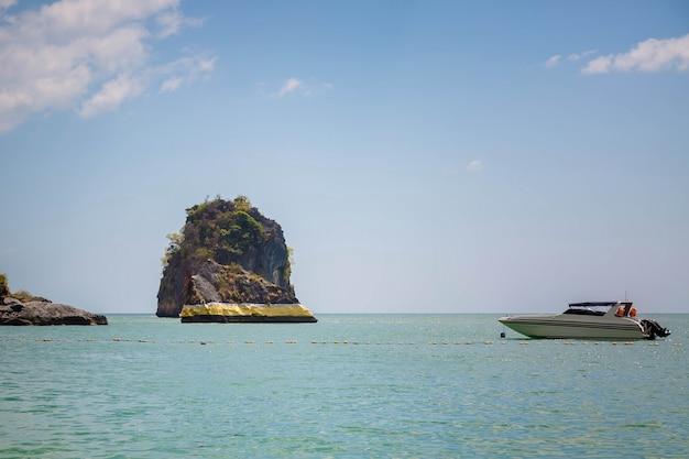 Roca en el mar de andaman pintura dorada espiritualidad tailandesa lancha rápida flota playa cueva pranang provincia de krabi