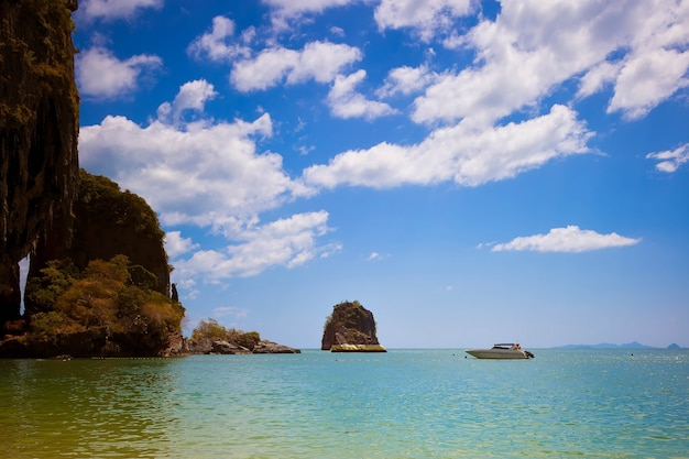Roca en el mar pintado con pintura dorada lancha rápida flota cerca de la playa de la cueva de pranang, provincia de krabi