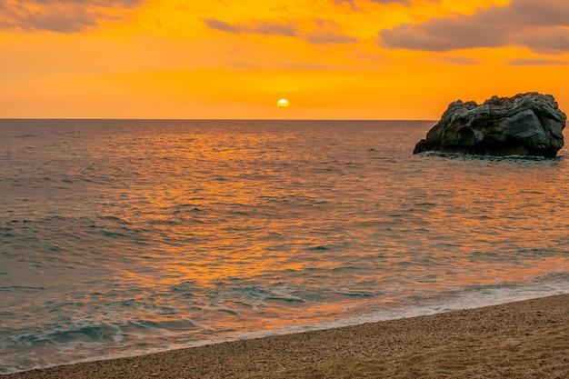 Roca solitaria en el mar cerca de la playa de arena. colorido amanecer sobre las tranquilas aguas de la costa mediterránea griega