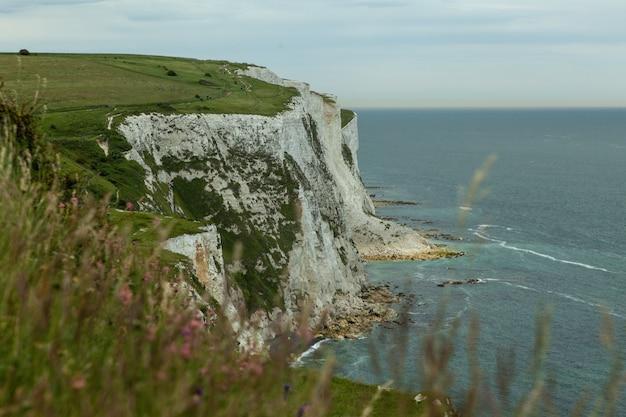 Rocas blancas cubiertas de vegetación rodeada por el mar en la costa sur de foreland en el reino unido
