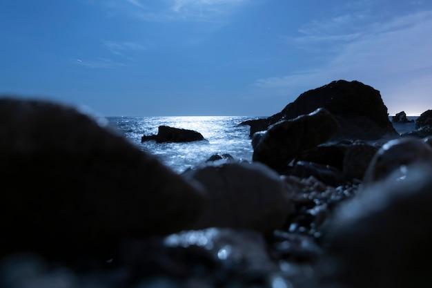 Rocas borrosas en el agua por la noche