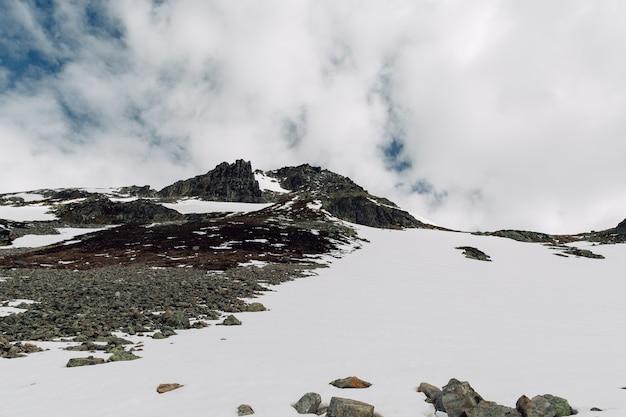 Rocas cubiertas de nieve en verano en los alpes suizos