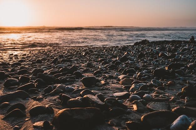 Rocas de playa arrastradas por las olas del océano.
