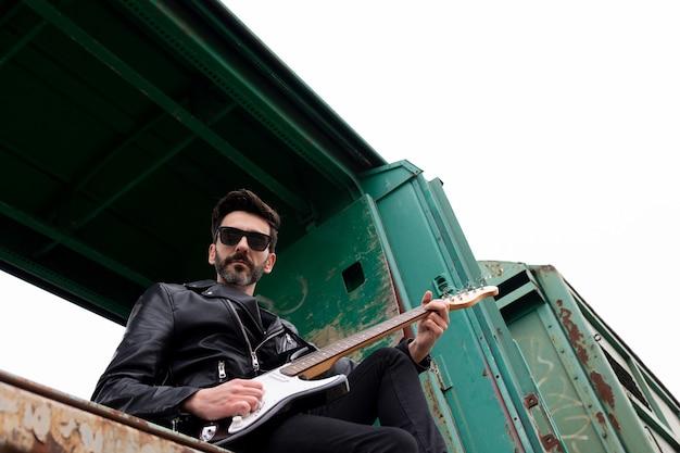 Rocker con gafas de sol y guitarra eléctrica sentado en un vagón de tren abandonado