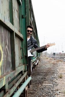 Rocker con gafas de sol y guitarra eléctrica subió a un vagón de tren abandonado