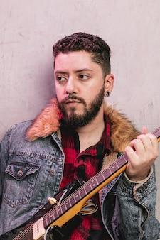 Rocker vestido vintage tocando la guitarra eléctrica