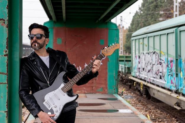Rockero con gafas de sol y guitarra eléctrica fumando un cigarrillo y jugando en un vagón de tren abandonado