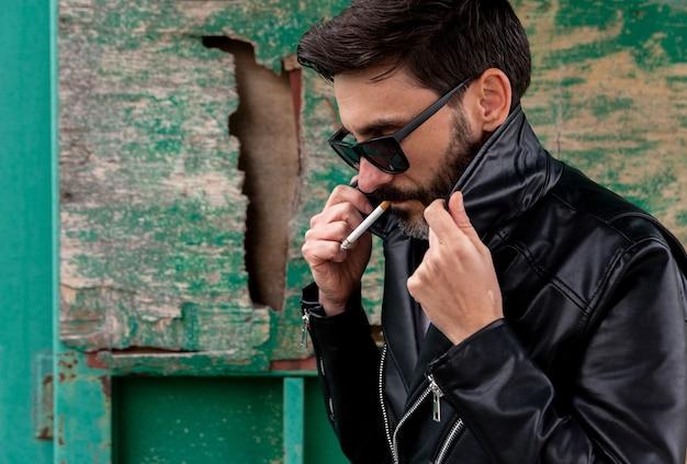 Rockero con gafas de sol y guitarra eléctrica fumando un cigarrillo en un vagón de tren abandonado