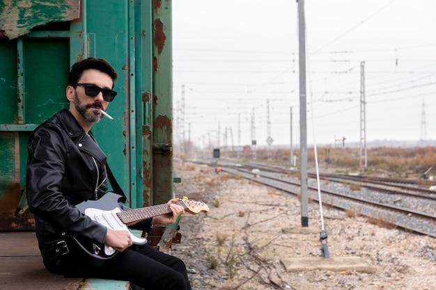 Rockero con gafas de sol y guitarra eléctrica sentado y fumando en un vagón de tren abandonado