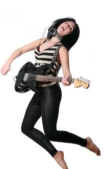 Rockero mujer saltando y tocando la guitarra eléctrica