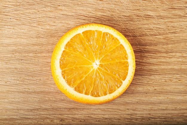 Una rodaja de limón, aislada en una madera.
