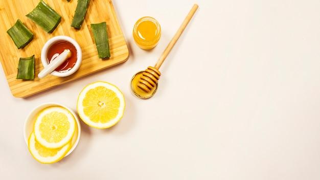 Rodaja de limón y aloevera con miel sobre fondo blanco
