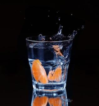 Rodaja de limón chapoteando en un vaso de agua con un chorro de gotas de agua en movimiento suspendido en el aire sobre el vaso sobre un fondo oscuro.