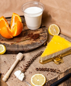 Una rodaja de limón, crema de naranja cheesecake con leche.