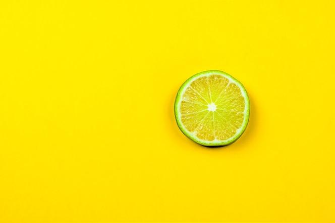 Rodaja de limón fresco sobre fondo amarillo brillante