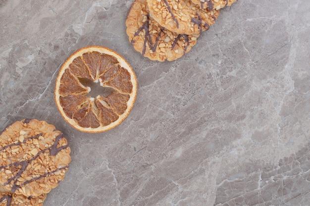 Rodaja de limón seco y galletas en mármol