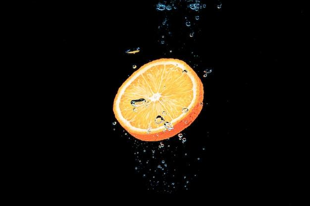Rodaja de naranja bajo el agua con burbujas sobre fondo negro