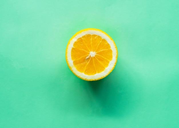 Rodaja de naranja sobre fondo verde.
