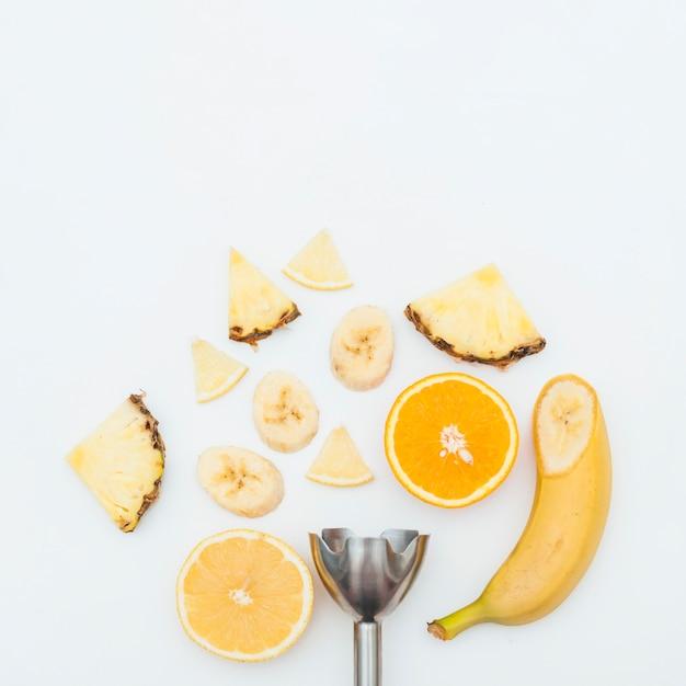 Rodaja de piña; plátano; rodajas de naranja con batidora eléctrica de acero inoxidable sobre fondo blanco