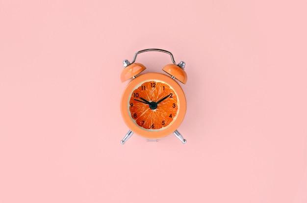 Rodaja de pomelo fresco en pequeño reloj despertador naranja