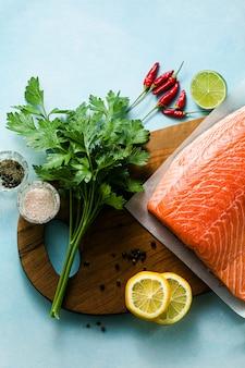 Rodaja de salmón fresco en una tabla de cortar de madera con hierbas aromáticas frescas y espárragos sobre la mesa. receta de cocina. fondo de alimentos. productos de pescado fresco