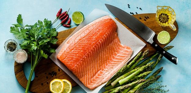 Rodaja de salmón fresco en una tabla de cortar de madera con hierbas aromáticas frescas y espárragos sobre la mesa. receta de cocina.