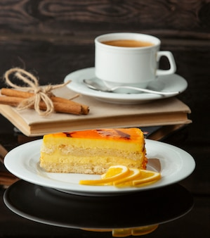 Una rodaja de tarta de limón con una taza de té.